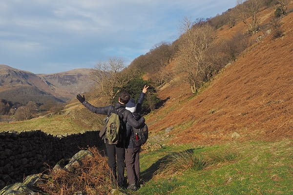 Photograph of a young couple with the backs turned to the camera, arms in the air, standing in the middle of the Lake District surrounded by trees and mountains